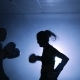 Young Woman Training with a Coach in a Boxing Club in a Smoky Gym - VideoHive Item for Sale