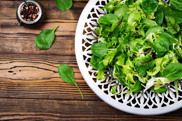 Fresh leaves of mix salad in a bowl on a wooden background. Flat lay. Top view - Stock Photo - Images