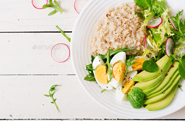 Healthy breakfast. Dietary menu. Oatmeal porridge and avocado salad and eggs. Top view - Stock Photo - Images