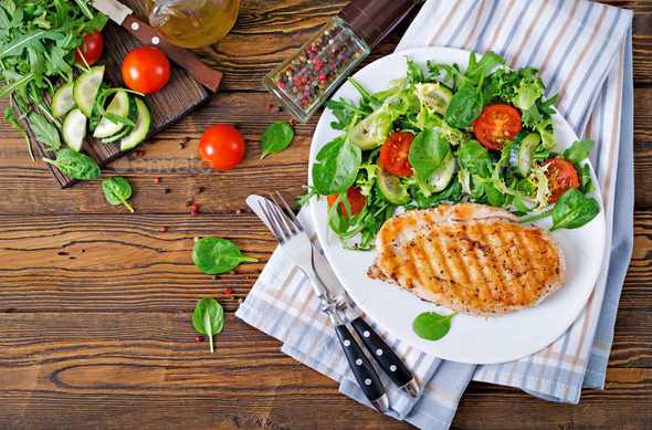 Grilled chicken breast and fresh vegetable salad - tomatoes, cucumbers and lettuce leaves. - Stock Photo - Images