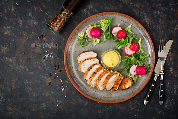 Baked chicken breast and fresh vegetables on the plate on a dark background. - Stock Photo - Images