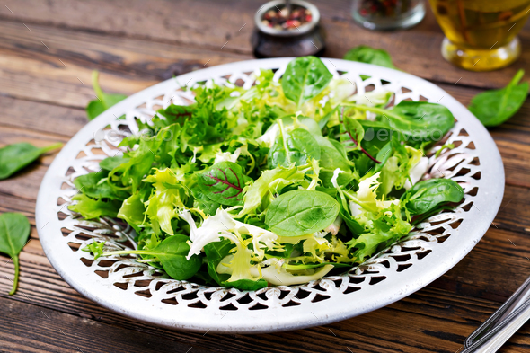Fresh leaves of mix salad in a bowl on a wooden background - Stock Photo - Images