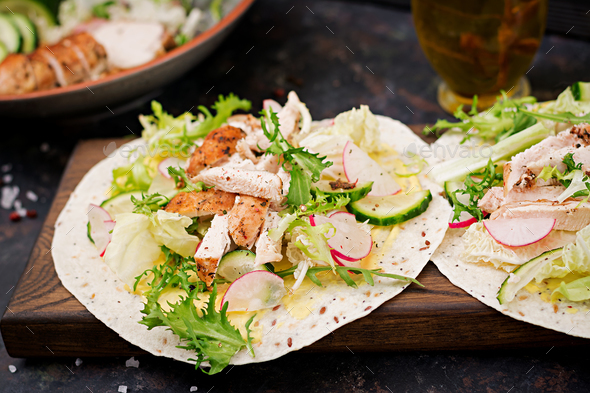 Healthy mexican tacos with baked chicken breast, cucumber, radish and lettuce. - Stock Photo - Images