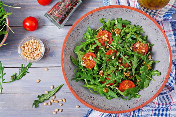 Dietary menu. Vegan cuisine. Healthy salad with arugula, tomatoes and pine nuts. Flat lay. Top view - Stock Photo - Images