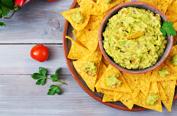 Guacamole avocado, lime, tomato, onion and cilantro, served with nachos  - Stock Photo - Images