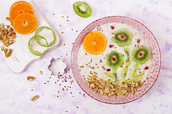 Tasty and healthy oatmeal porridge with kiwi, pomegranate and nuts.  - Stock Photo - Images