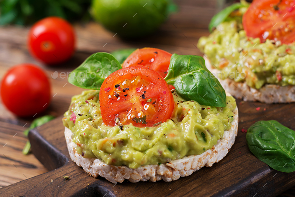 Healthy breakfast. Sandwich crisp bread with guacamole and tomatoes on a wooden background. - Stock Photo - Images