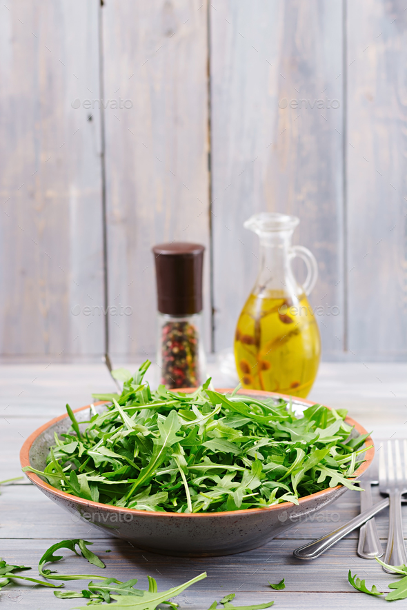 Fresh leaves of arugula in a bowl on a light wooden background - Stock Photo - Images