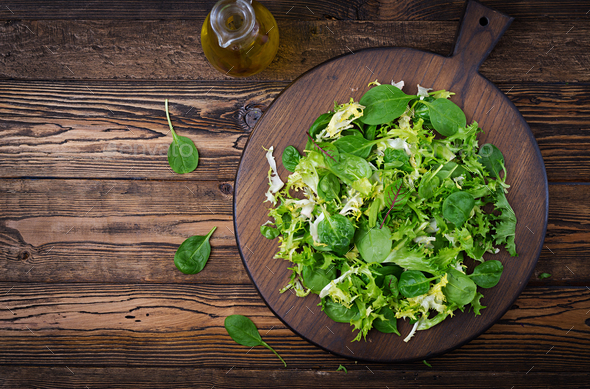 Fresh leaves of mix salad on a wooden background. Flat lay. Top view - Stock Photo - Images