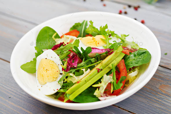 Delicious and light salad of tomatoes, eggs and a mix of lettuce leaves. Healthy breakfast. - Stock Photo - Images