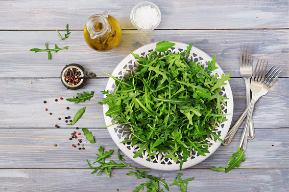 Fresh leaves of arugula in a bowl on a light wooden background. Flat lay. Top view - Stock Photo - Images