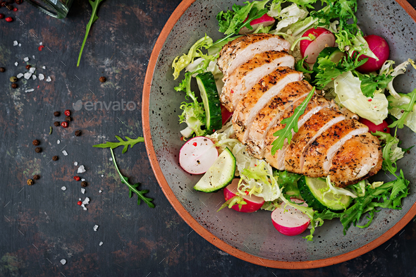 Bowl with salad of fresh vegetables and baked chicken breast on a dark background.  - Stock Photo - Images