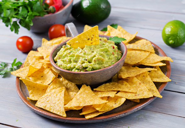 Guacamole avocado, lime, tomato, onion and cilantro, served with nachos - Traditional Mexican snack - Stock Photo - Images