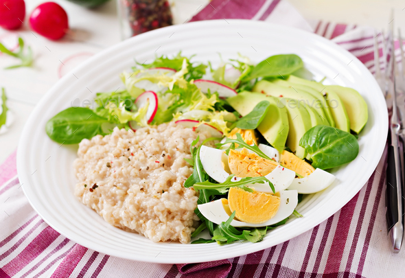 Healthy breakfast. Dietary menu. Oatmeal porridge and avocado salad and eggs. - Stock Photo - Images