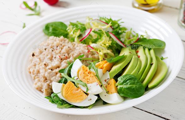 Healthy breakfast. Dietary menu. Oatmeal porridge and avocado salad and eggs. - Stock Photo - Images