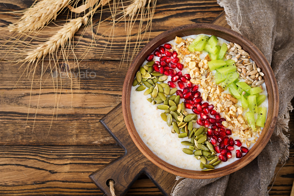 Delicious and healthy oatmeal with kiwi, pomegranate and seeds.  - Stock Photo - Images