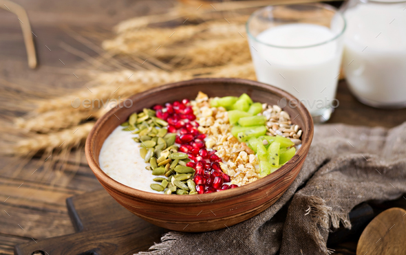 Delicious and healthy oatmeal with kiwi, pomegranate and seeds - Stock Photo - Images