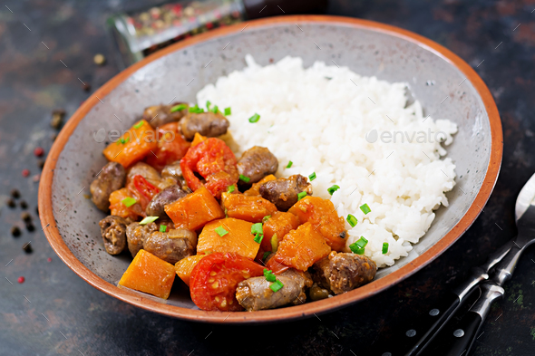 Chicken hearts with pumpkin and tomatoes in tomato sauce. The garnish is served with boiled rice. - Stock Photo - Images