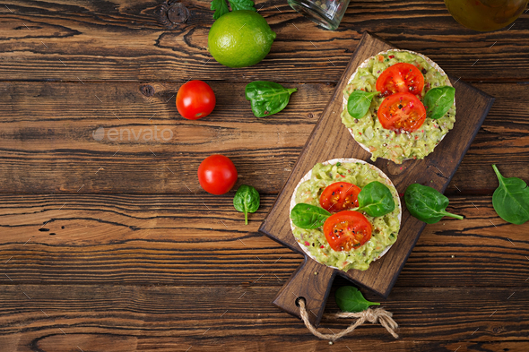 Healthy breakfast. Sandwich crisp bread with guacamole and tomatoes - Stock Photo - Images
