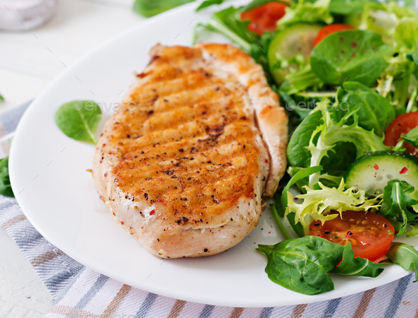 Grilled chicken breast and fresh vegetable salad - tomatoes, cucumbers - Stock Photo - Images
