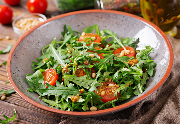 Dietary menu. Vegan cuisine. Healthy salad with arugula, tomatoes and pine nuts. - Stock Photo - Images