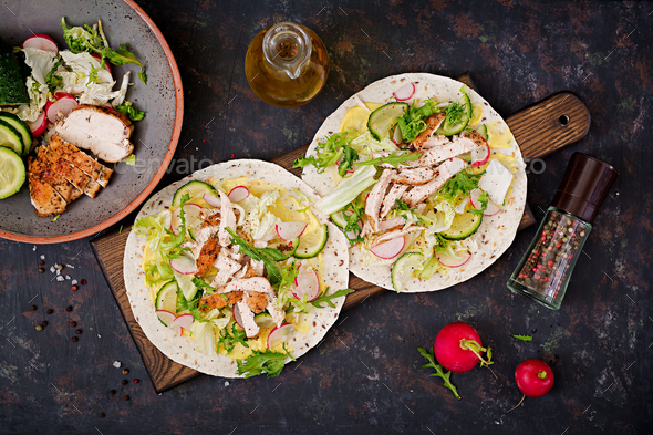 Healthy mexican tacos with baked chicken breast, cucumber, radish and lettuce. Flat lay. Top view - Stock Photo - Images