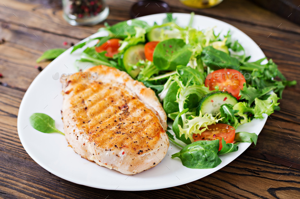 Grilled chicken breast and fresh vegetable salad - tomatoes, cucumbers and lettuce  - Stock Photo - Images