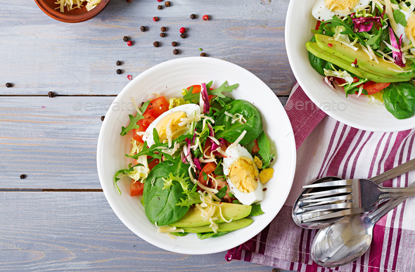 Delicious and light salad of tomatoes, eggs and a mix of lettuce leaves. Healthy breakfast. Top view - Stock Photo - Images