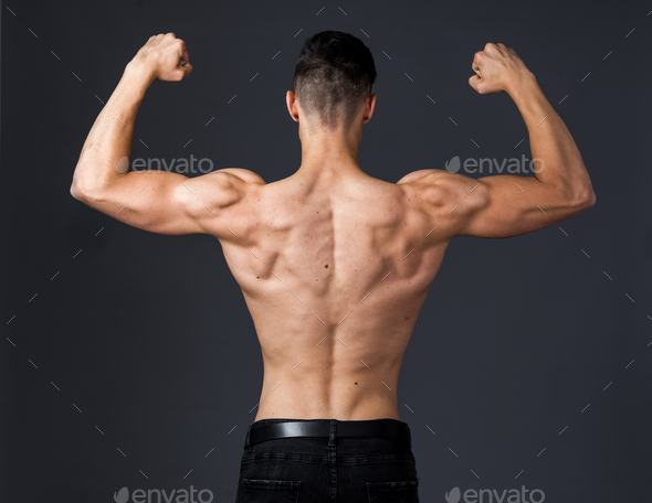 Muscular young man poses in studio with jeans and shirtless - Stock Photo - Images