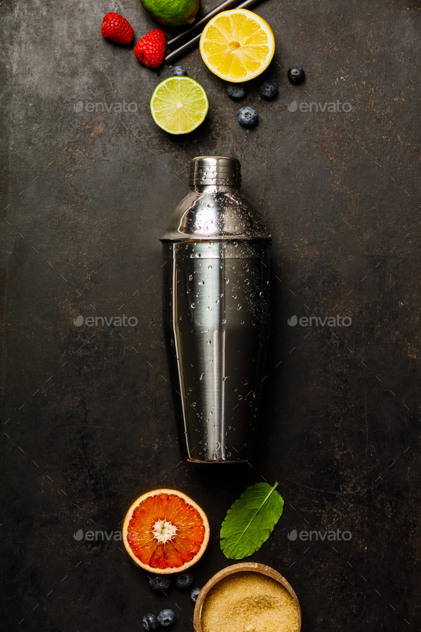 Cocktail shaker, tropical fruits and leaves on a dark background - Stock Photo - Images
