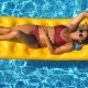 Top View of Beautiful Tanned Girl in Sunglasses and Red Bikini Lying on Yellow Inflatable Mattress - VideoHive Item for Sale