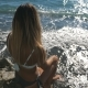 Rear Back View of Unrecognizable Young Girl in Bikini Sitting on Stone Near Seashore and Looking - VideoHive Item for Sale