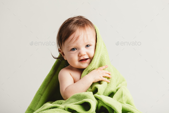 Cute little baby leaning out of cozy green blanket. - Stock Photo - Images