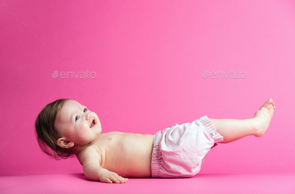 Baby girl laying on her back, trying to get up. - Stock Photo - Images