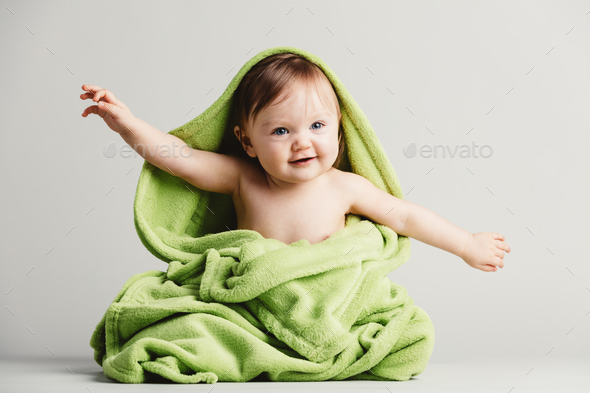 Baby covered in green blanket in a funny pose. - Stock Photo - Images