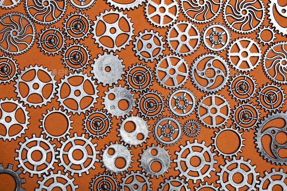 Bunch of cogwheels on an orange background. - Stock Photo - Images