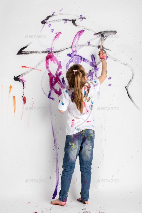 Little girl decorating a white wall with paint - Stock Photo - Images