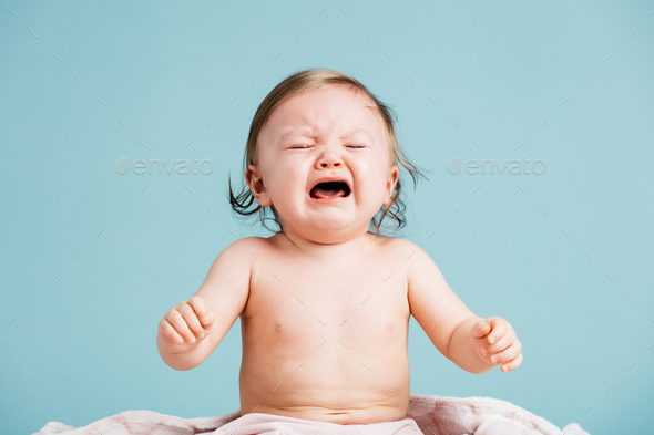 Sad baby sitting down and crying. - Stock Photo - Images