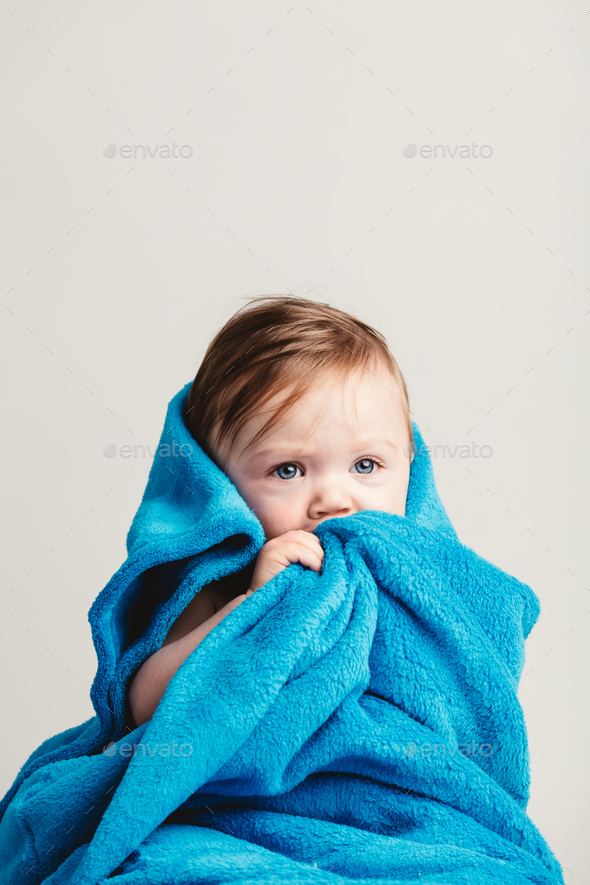 Little baby girl tucked in a cozy blue blanket. - Stock Photo - Images