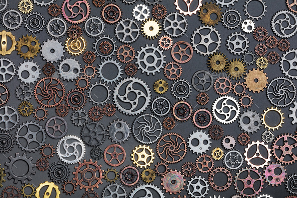 Different cogwheels laying on grey background. - Stock Photo - Images