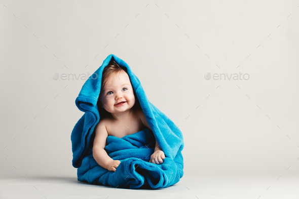 Baby girl covered with a blue warm blanket - Stock Photo - Images