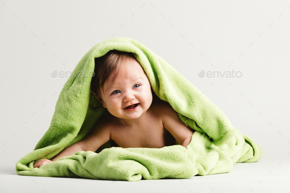 Baby girl covered with green warm blanket - Stock Photo - Images