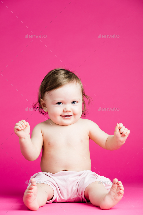 Joyful toddler on a pink background. - Stock Photo - Images