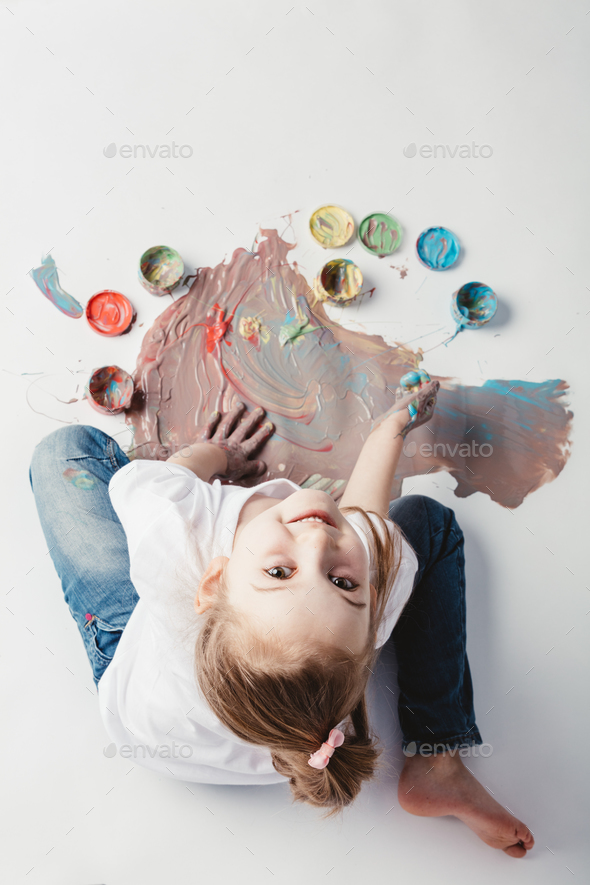 Little girl painting with her hands on the floor. - Stock Photo - Images