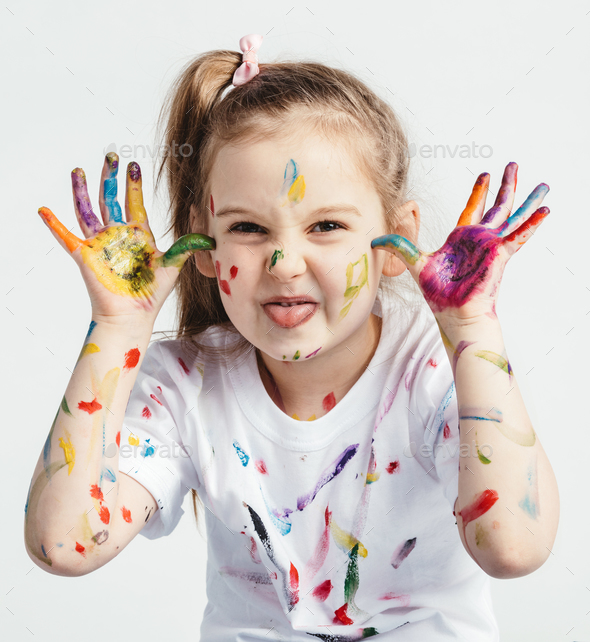Little girl covered in paint making funny faces. - Stock Photo - Images