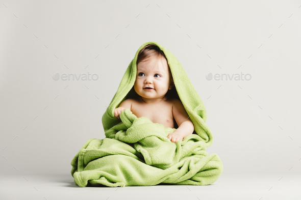 Cute baby girl covered in green blanket. - Stock Photo - Images