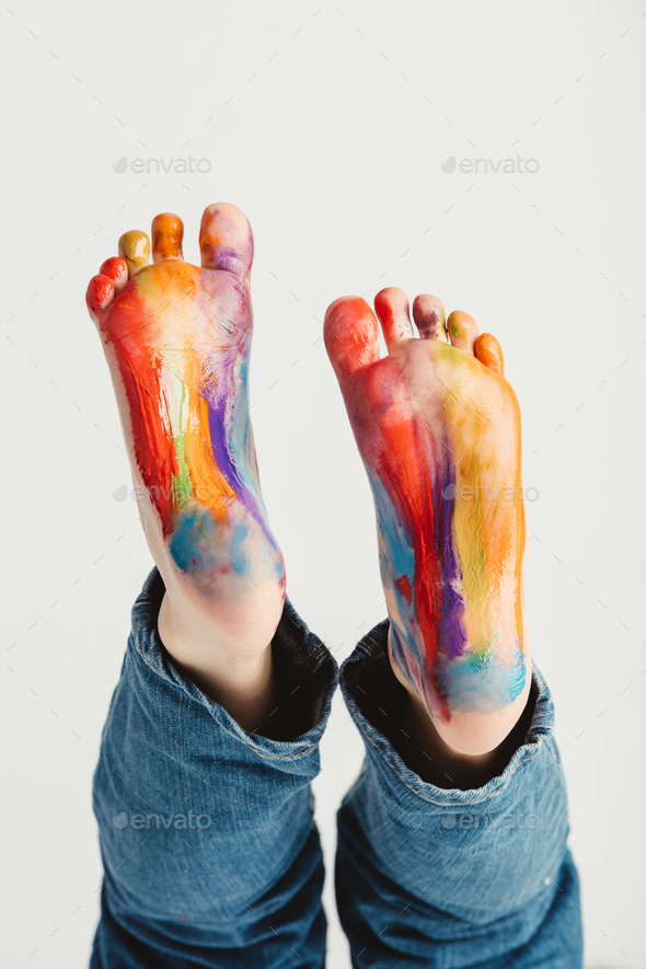 Kid's feet painted in rainbow colors. - Stock Photo - Images