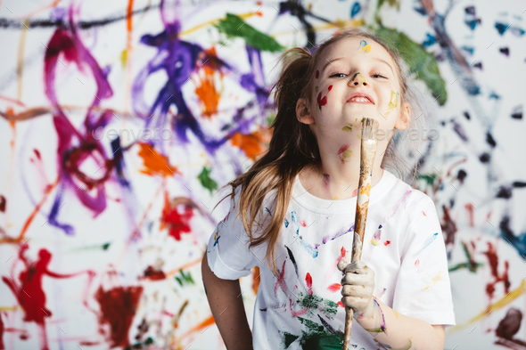 Young child painter standing with a brush - Stock Photo - Images