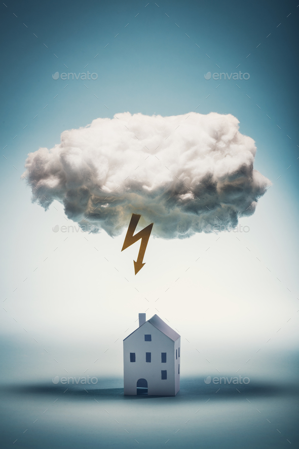 Paper house standing under a white cloud with yellow lightning - Stock Photo - Images