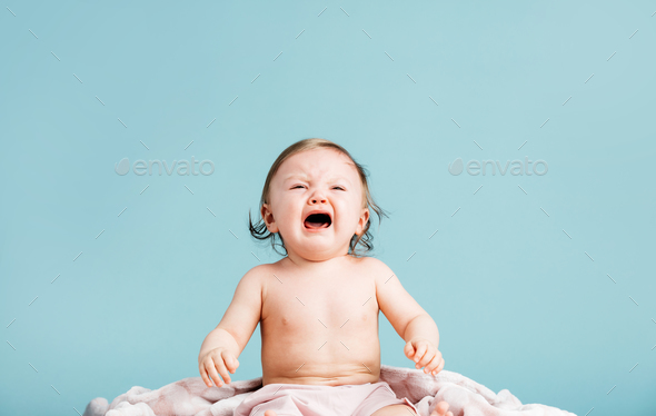 Crying baby girl sitting on a blanket - Stock Photo - Images